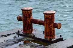 Old rusty metal bollard pier - device for yacht mooring Stock Photos