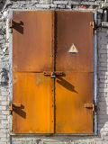 Old rusty metal door to the substation with a cautiously electricity Royalty Free Stock Photography