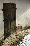 Old rusty metal door with two latches, stone pathway and snow. House is painted with fading white color. Afternoon sunshine is present royalty free stock image