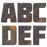 Old rusty metal english alphabet, numbers and signs. Isolated Royalty Free Stock Image
