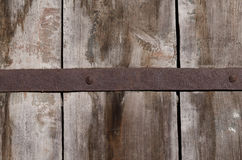 An old rusty metal fastener centered on large wooden boards Royalty Free Stock Photography