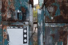 Old and rusty metal gate lock with traces of paint and paper royalty free stock images