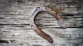Old rusty metal horseshoe for good luck pinned and nailed on a wooden texture surface royalty free stock images