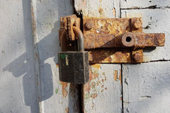 An old rusty metal latch with an iron lock on wooden door, painted with white paint, an empty place for text. Stock Image