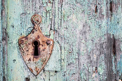 Old rusty metal lock and keyhole on a old turquoise wooden door. As a beautiful vintage background Stock Photos