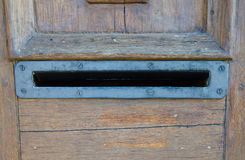 Old rusty metal opened mailbox in the wooden doors with no letters inside royalty free stock image
