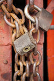 Old rusty metal padlocks on chains. Two old heavy duty metal padlocks and chain used to secure a red gate on a shopfront in bangkok thailand Stock Photo