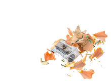 Old rusty metal pencil sharpener and different colour shavings. Royalty Free Stock Photos