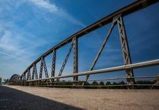 Rusty metal railings on the bridge over the river on sunny d. Old rusty metal railings on the bridge over the river on sunny day. Road with cracked asphalt stock images