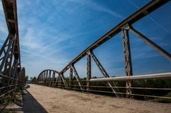 Rusty metal railings on the bridge over the river on sunny d. Old rusty metal railings on the bridge over the river on sunny day stock photography