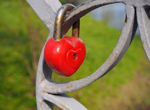Old rusty metal red heart lock, the romantic symbol of never ending love hanging on the fence of bridge. Love forever through time concept royalty free stock photo