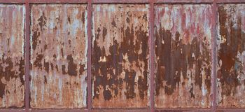 Old rusty metal wall with cracked red paint, texture background.  Stock Photo