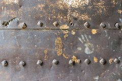 Old and rusty metal wall surface with big rivets royalty free stock photo