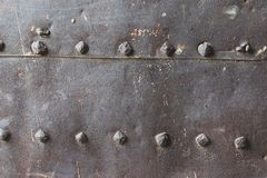 Old and rusty metal wall surface with big rivets stock photography