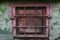 old rusty metal window with grating on a peeling wall royalty free stock photography