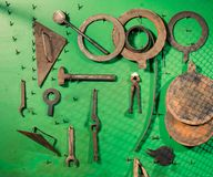 Old rusty metallic instruments and tools. On green wall panel royalty free stock photography