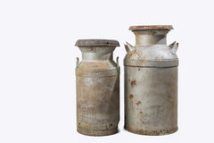 Old rusty milk cans isolated on white. Two antique rusty milk containers used with cream separators Stock Images