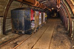 Old and rusty mine train for personnel transfer parked in mine tunnel with wooden timbering royalty free stock photos
