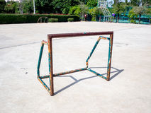 Old and rusty mini soccer football goal on basketball concrete f. Loor  in the afternoon Stock Photos