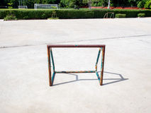 Old and rusty mini soccer football goal. On basketball concrete floor  in the afternoon Stock Image