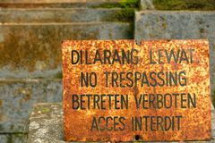 Old and rusty multilingual no treppasing sign Stock Photos