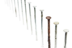 Old rusty nail between new ones Stock Photos