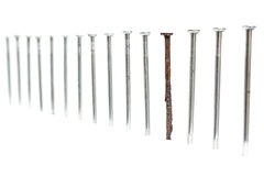 Old rusty nail between new ones Royalty Free Stock Photos
