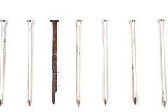 Old rusty nail and new ones. Old rusty nail between new ones. Weak point metaphor Royalty Free Stock Photo