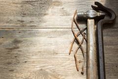 Old rusty nails and hammer. Nail puller on wooden background, space for text Stock Photo