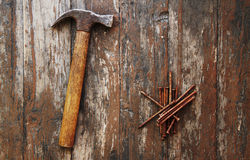 Old rusty nails and hammer. On wooden background Stock Photo