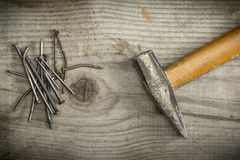 Old rusty nails and a hammer. Old rusty nails and hammer on wooden background Royalty Free Stock Photography