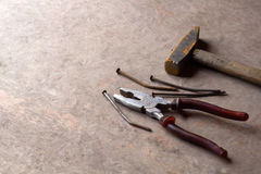 Old rusty nails, pliers and hammer. On a wooden background Stock Photo