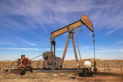 Old rusty oil well pump jack sitting in field with bright blue dramatic sky - head of machinery looks like a funny face stock images