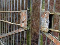 Old rusty open gate with broken lock, ajar stock image
