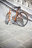 Old rusty orange bicycle against a marble wall Stock Images