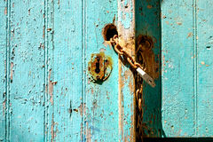 Old rusty padlock and chain on weathered textured door Royalty Free Stock Photography
