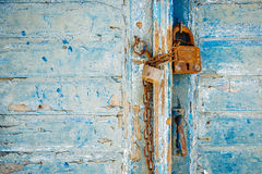 Old rusty padlock and chain on weathered textured door Stock Photo