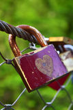 Old and rusty padlock hanging on the bridge. Stock Photos