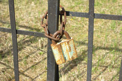 Old rusty padlock on metal fence close up Stock Photography