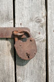 Old rusty padlock. On a wooden door stock photo