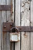 Old rusty padlock on wooden door Stock Image