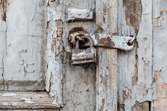 Old rusty padlock on old wooden door. Wooden door with peeling paint closed on a large iron padlock. Peeling paint on door stock photography