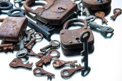 Old rusty padlocks and keys on white background. Mirror.  Stock Photos