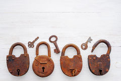 Old rusty padlocks and keys on a wooden background Stock Photography