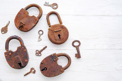 Old rusty padlocks and keys on a wooden background Stock Images