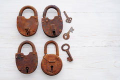 Old rusty padlocks and keys on a wooden background Stock Photo