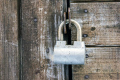 Old rusty painted metal padlock on wooden board door closeup Royalty Free Stock Photos