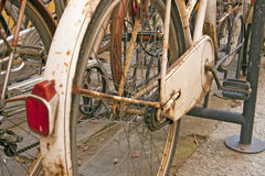 Old rusty parked bicycle in Italian town. With other bicycles Royalty Free Stock Photo
