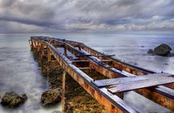 Old rusty pier in a cloudy day stock photo