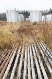 Old rusty pipes and tanks. At an abandoned oil refinery Royalty Free Stock Image